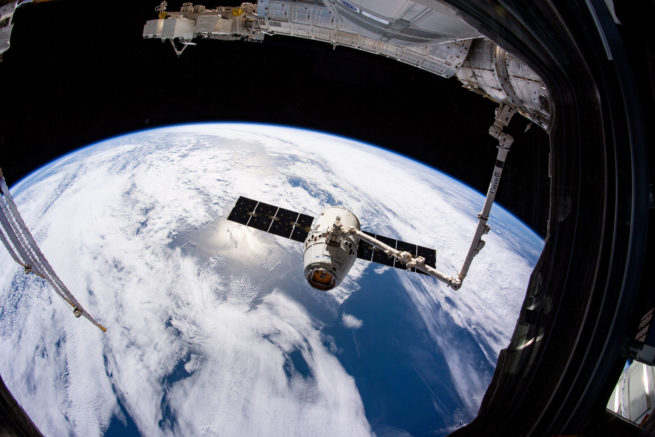 Vu depuis la fenêtre de la Station spatiale internationale: le bras Canadarm2 attrapant le vaisseau-cargo Dragon de SpaceX. (Source : NASA/Anne McClain.)